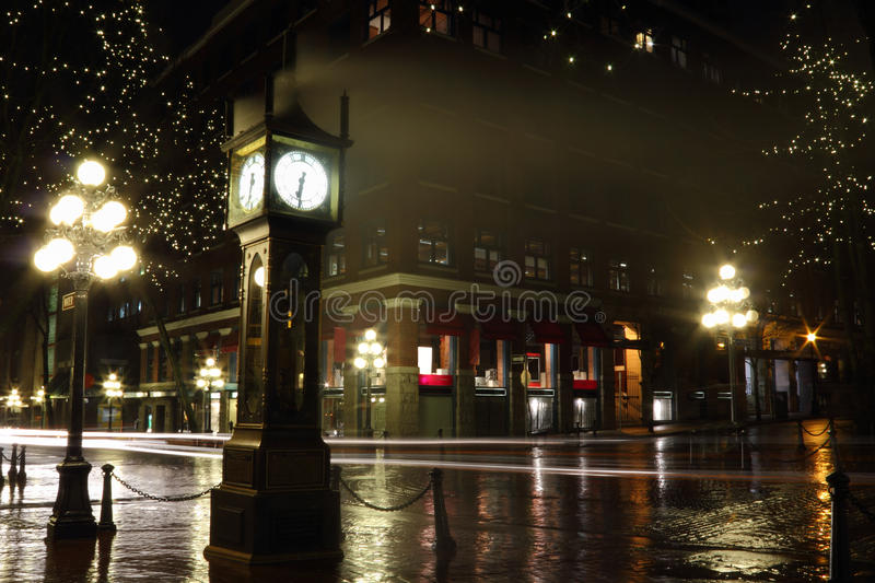 Gastown at Night, Vancouver. Reflections on the wet street during a rainy night in Vancouver's touristy Gastown district at the steam clock. The streaks of light stock images