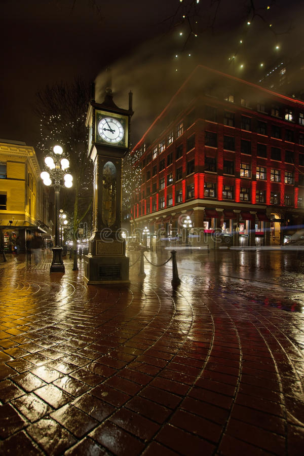 Gastown Steam Clock on a Rainy Night Vertical. Gastown Steam Clock in Vancouver BC Canada on a Rainy Night with Historic Red Building stock image