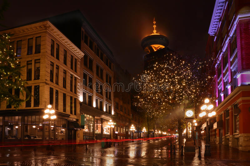 Gastown Vancouver Night, BC, Canada. Reflections on a rainy night in Vancouver's famous Gastown district. The streaks of light are from vehicles crossing the stock photo