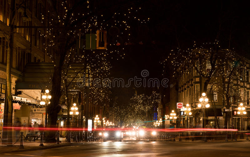 Gastown, Vancouver at night. Vancouver, Canada - January 28, 2017: Gastown, Vancouver at night with lights in the trees and light trails from the traffic royalty free stock photo
