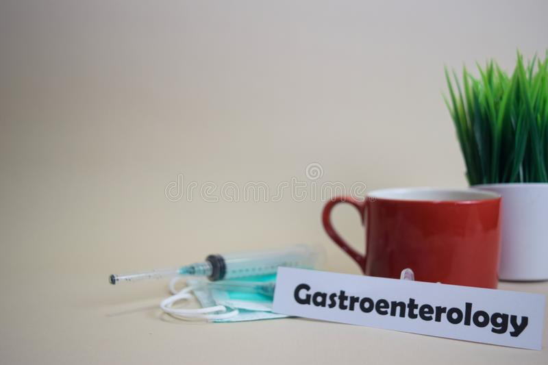 Gastroenterology text, grass pot, coffee cup, syringe, and face green mask. royalty free stock photos