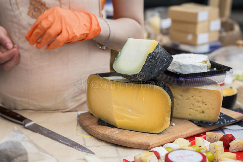 Gastronomic products for gourmets, traditional italian cut cheese heads on market counter, woman hands of seller with. Gastronomic products for gourmets royalty free stock photography