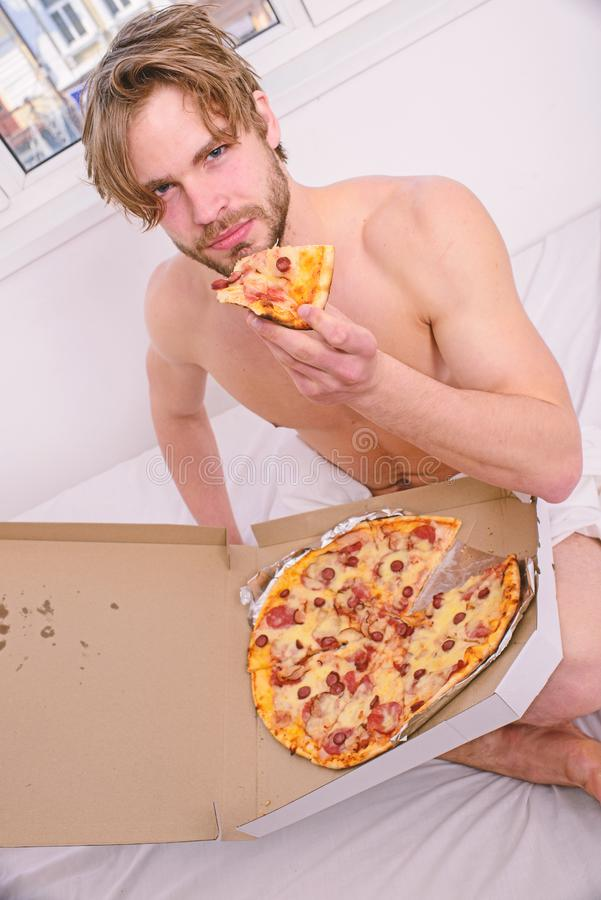 Gastronomic satisfaction. Man bearded handsome eat pizza. Man eat pizza breakfast. Guy naked covered pizza box sit bed. Bedroom offer you join him. courier stock image