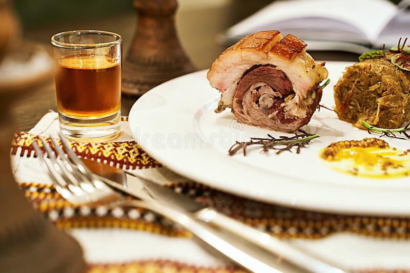 Gastronomiekonzept Haute Cuisine Traidiontal Westukrainische Schweinefleischroulade mit Bigos Jägern Eintopf und Tormentil vodka lizenzfreie stockbilder