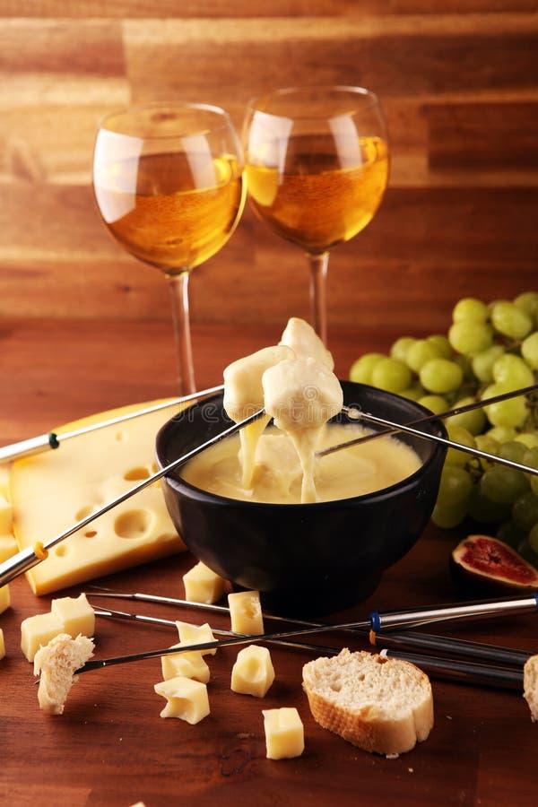 Gastronomisch Zwitsers fonduediner op een de winteravond met geassorteerde kazen op een raad naast een verwarmde pot van kaasfond royalty-vrije stock foto