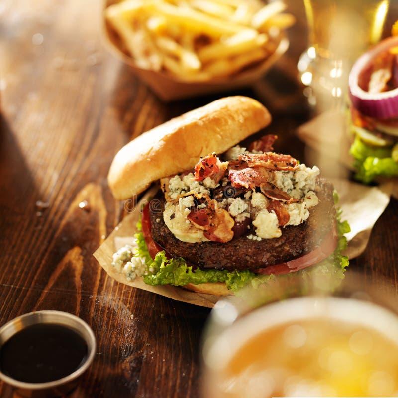 Gastronomische BLEU-kaasburgers met bier die worden gegoten royalty-vrije stock afbeelding