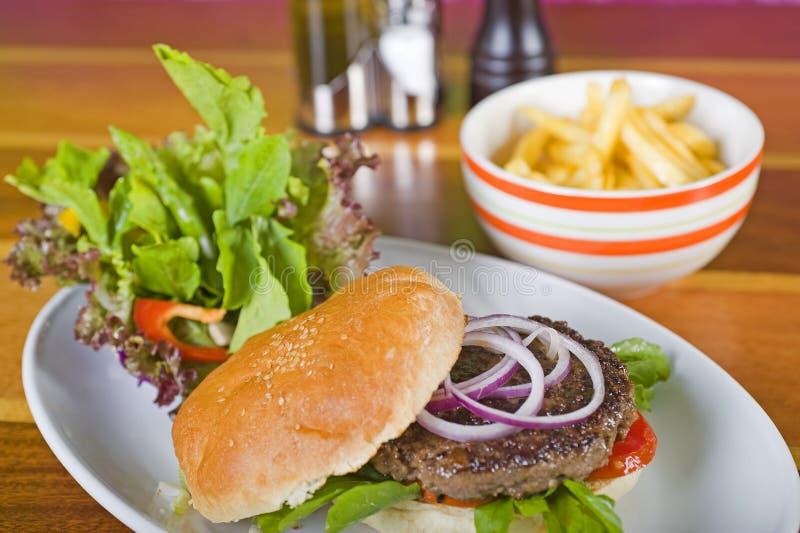 Gastronomische hamburger met salade en gebraden gerechten stock foto