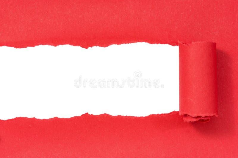 Gat dat in rood document wordt gescheurd stock foto