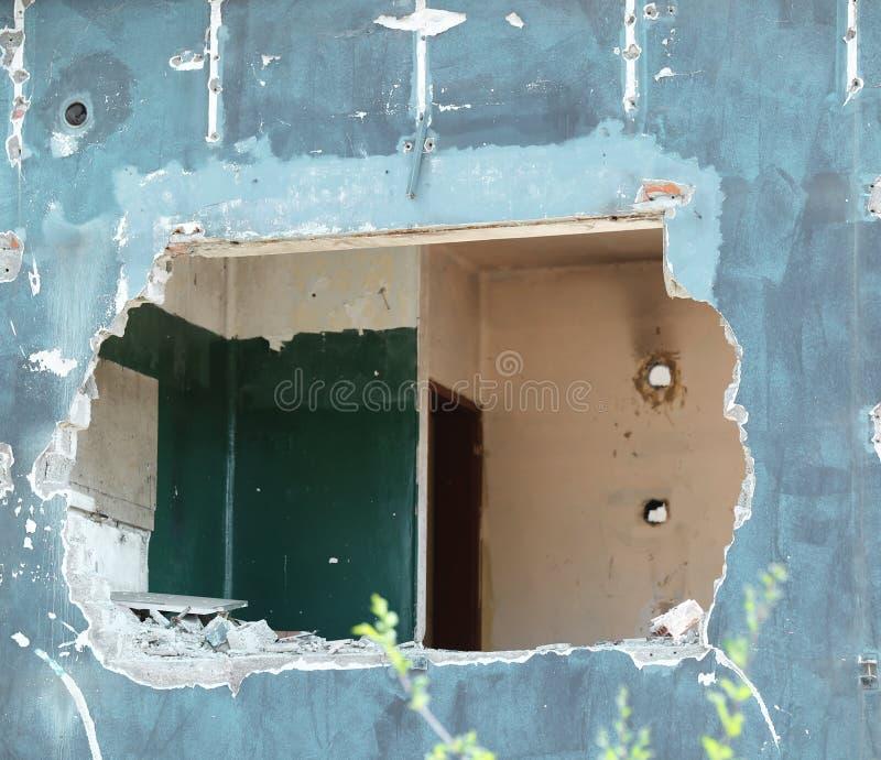Gat op de muur van het vernietigde huis stock foto's