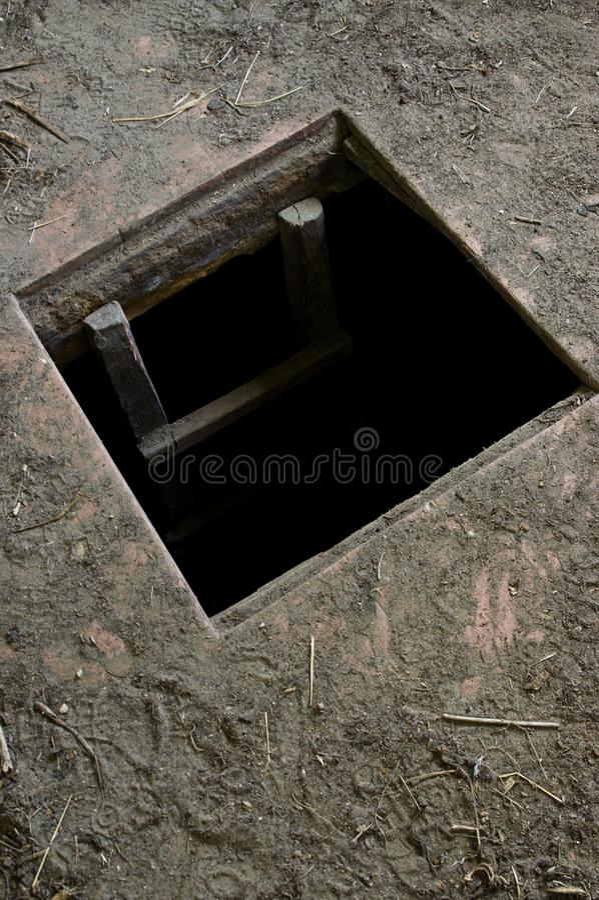Gat in vloer die van oud huis tot kelder leiden stock foto's