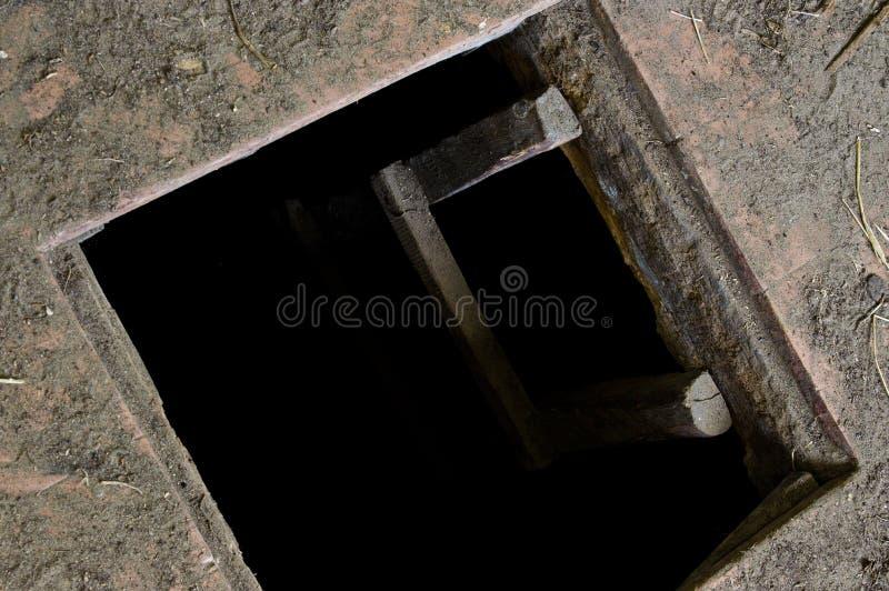 Gat in vloer die van oud huis tot kelder leiden stock foto