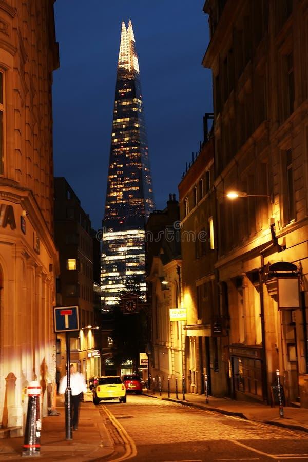 Gata av London på natten Skärvan av den Glass skyskrapan som byggs i arkitektonisk stil för Neo futurism arkivfoto