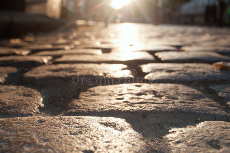 Gata i aftongarneringen med ljusa kulor, Augusti 2018 Lviv Ukraina väg från förberedande stenar i strålarna av inställningssolen royaltyfri fotografi