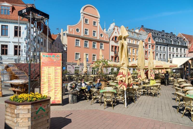 Gata i den historiska mitten med färgrika hus och stänger i gamla Riga, Lettland royaltyfri foto