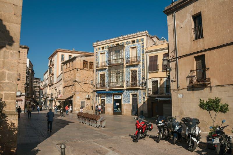 Gata med byggnader, ett av dem täckte vid färgrika keramiska tegelplattor i Caceres royaltyfri foto