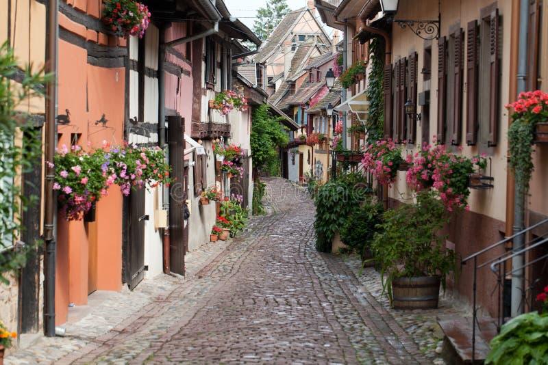 Gata med korsvirkes- hus i Eguisheim royaltyfri foto