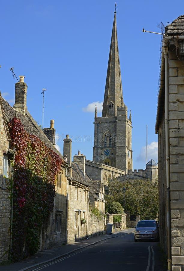Gata med kyrkan på Burford, Oxfordshire, England royaltyfri bild