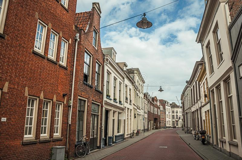 Gata med tegelstenhus och cyklar framme av dörrar royaltyfri bild