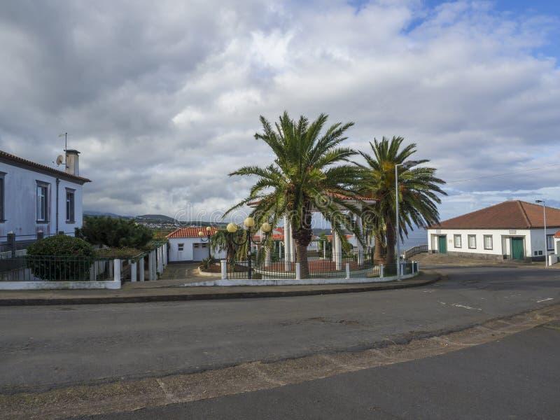 Gata och hus i azorean kolonial stil på den Nordeste byn med gröna palmträd och vita moln för blå himmel, Sao arkivfoto