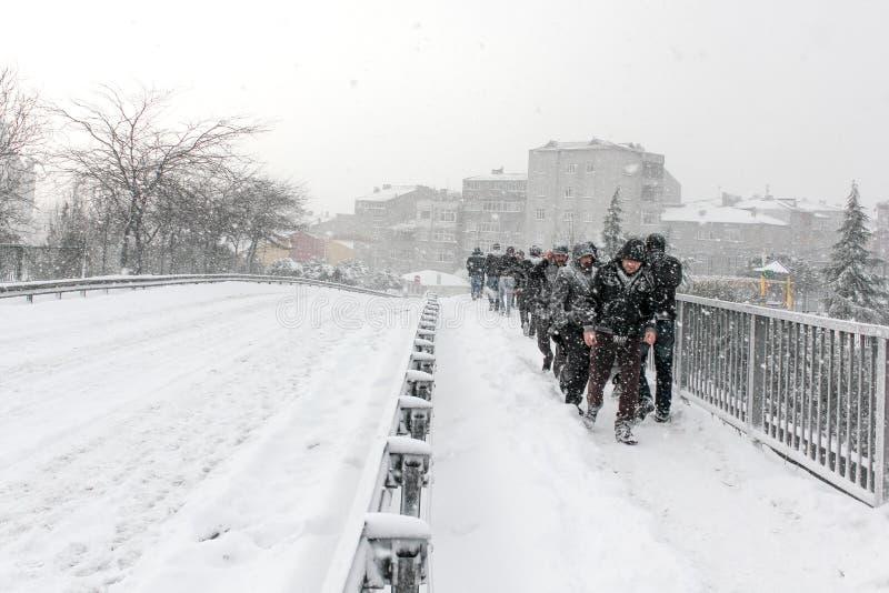 Gata som täckas med snö, och folk som går tungt snöfall arkivfoto