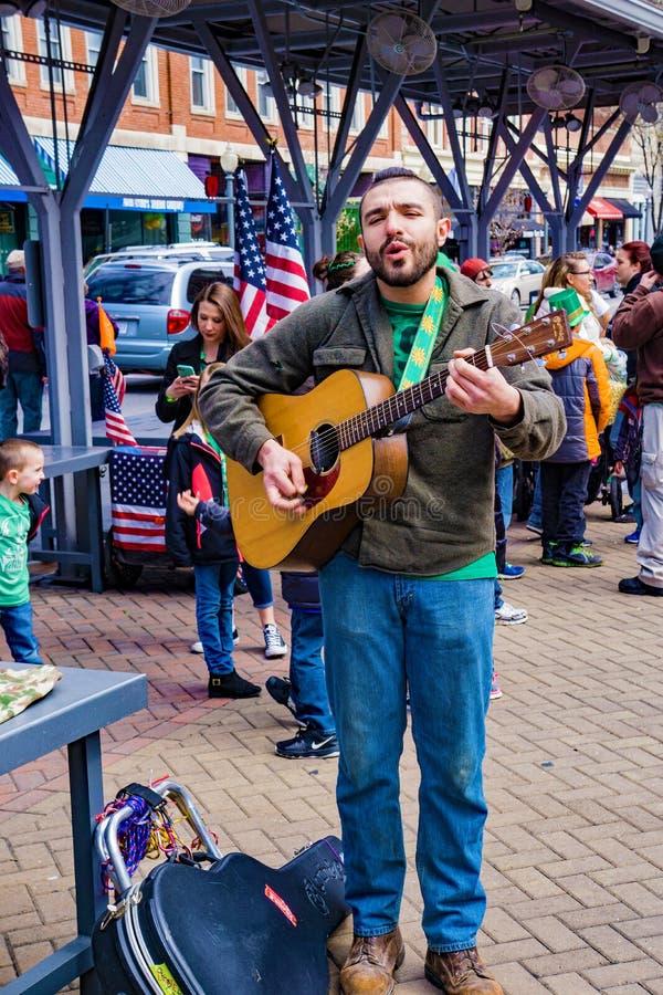 Gataaktör som sjunger och spelar en gitarr royaltyfri bild