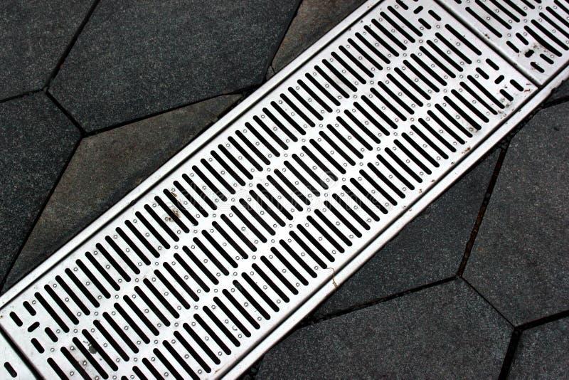 Gataavloppsränna av ett stormwaterdräneringsystem på en trottoar arkivfoton