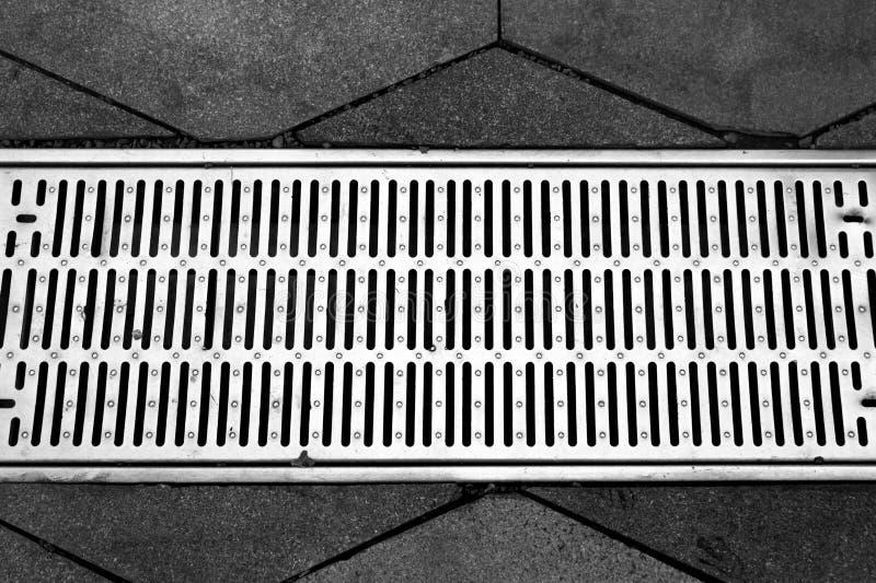 Gataavloppsränna av ett stormwaterdräneringsystem på en trottoar royaltyfri fotografi