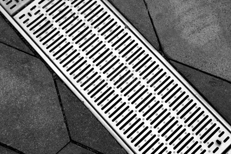 Gataavloppsränna av ett stormwaterdräneringsystem på en trottoar arkivbild