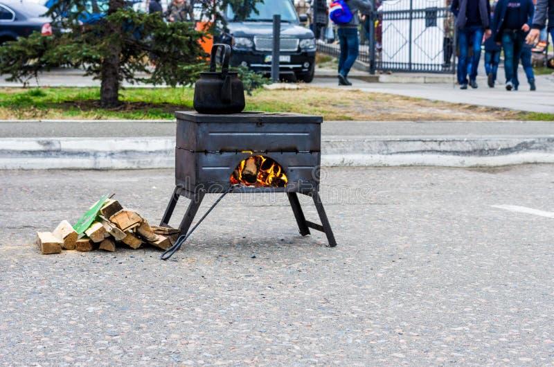 Gatafyrpanna med bränning brand Matlagningmat och te En gataugn med brand arkivfoton