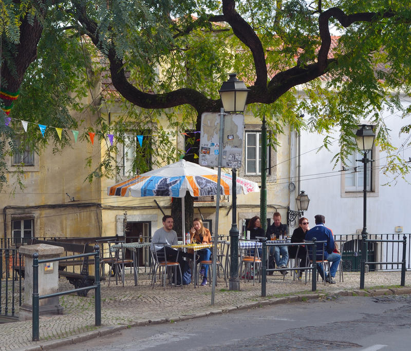 Gatakafé med folk på tabeller i det Alfama området Lissabon Portugal royaltyfria foton