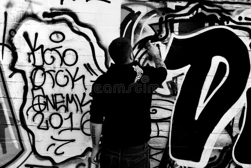 Gatakonstnären avslutar ett arbete på en vägg med sprejer under en konkurrens royaltyfri bild