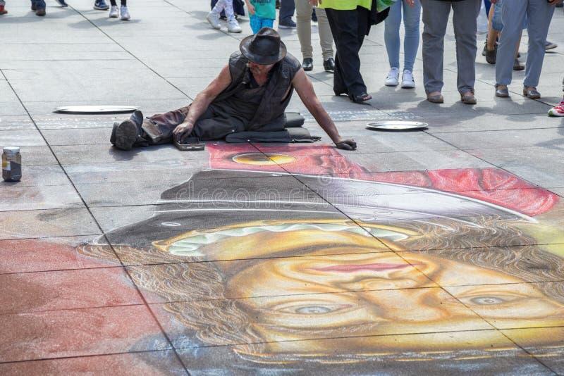 Gatakonstnären drar på trottoaren med krita royaltyfria foton