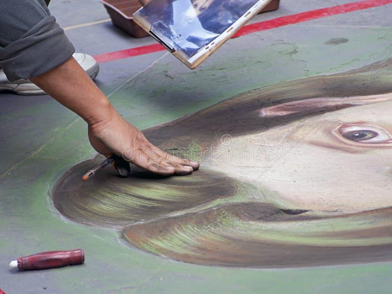 Gatakonstnären målar med krita på trottoaren arkivfoto