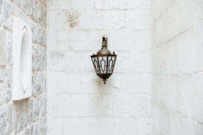Gatalampa p? den orange v?ggen Historisk lampa f?r svart metallgata p? en gammal gul orange v?gg royaltyfri fotografi