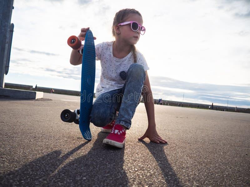 Gatalivstil: En flicka i rosa solglasögon och rosa gymnastikskor sitter på asfalten och rymmer en blå skateboard Portrtet royaltyfria foton
