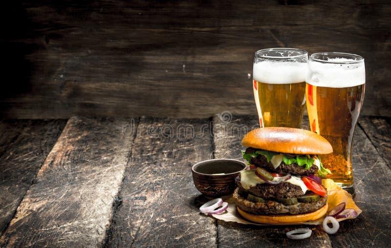 Gatamat En stor hamburgare med exponeringsglas av ljust öl arkivfoto