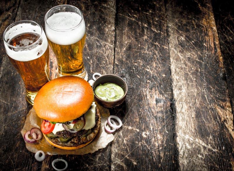 Gatamat En stor hamburgare med exponeringsglas av ljust öl royaltyfria foton