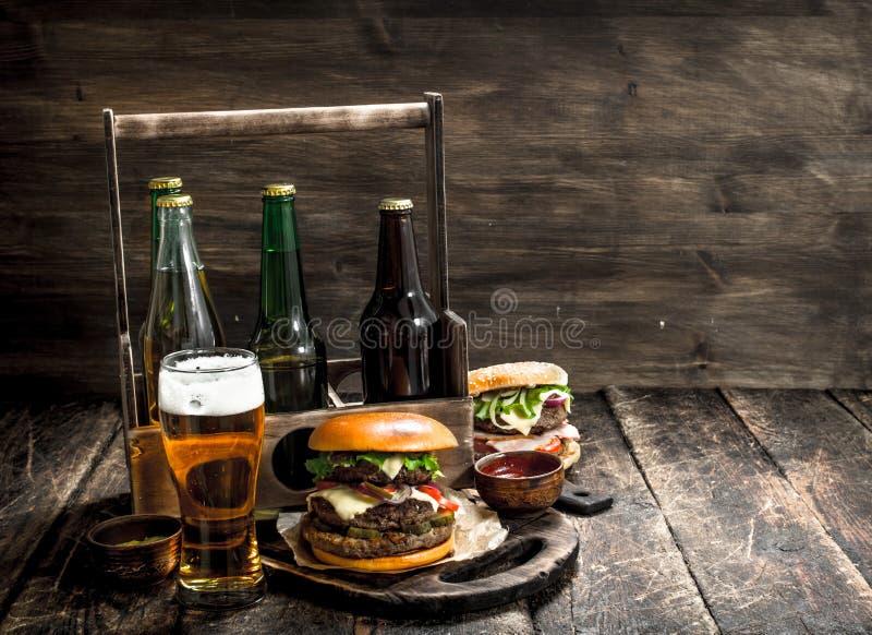 Gatamat Nya hamburgare med en ask av öl fotografering för bildbyråer