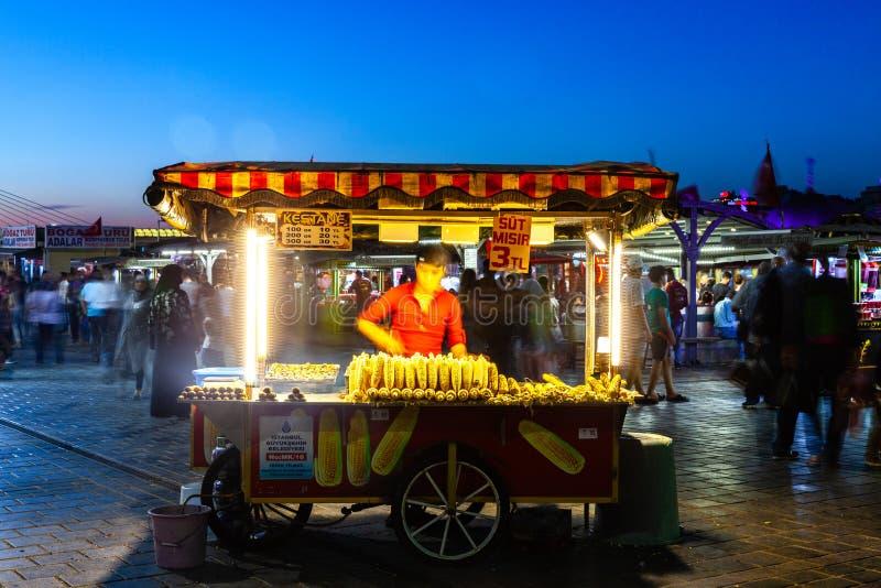 Gatamatförsäljaren säljer havremajskolvar och grillade kastanjer på arkivfoton