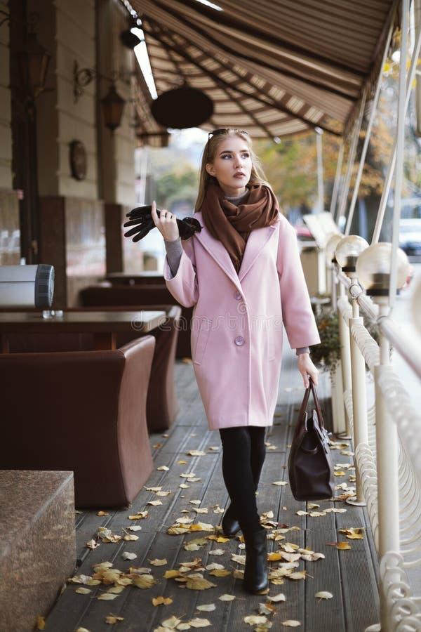 Gatamodebegrepp: full kroppstående av det bärande rosa färglaget för ung härlig kvinna med handväskan som går i staden royaltyfri fotografi