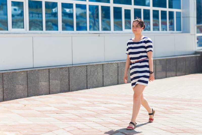 Gatamodebegrepp härligt stadskvinnabarn Härlig flicka som bär den gjorde randig klänningen som går på gatan royaltyfri foto