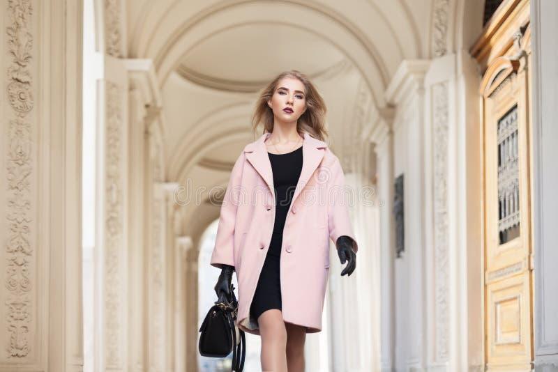 Gatamodebegrepp: stående av det bärande rosa färglaget för ung härlig kvinna med handväskan som går i staden modell royaltyfria bilder