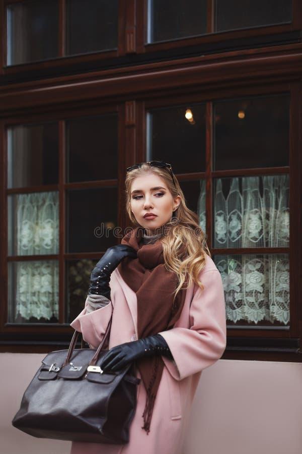 Gatamodebegrepp: stående av det bärande rosa färglaget för ung härlig kvinna med handväskan som poserar på fönstret Stad arkivbild