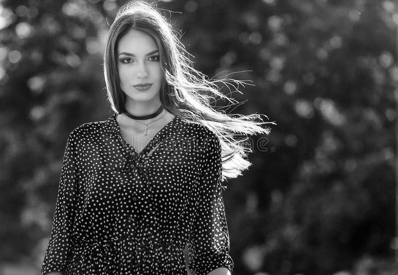 Gatamodefoto av den unga eleganta kvinnan med att smickra lonh fotografering för bildbyråer