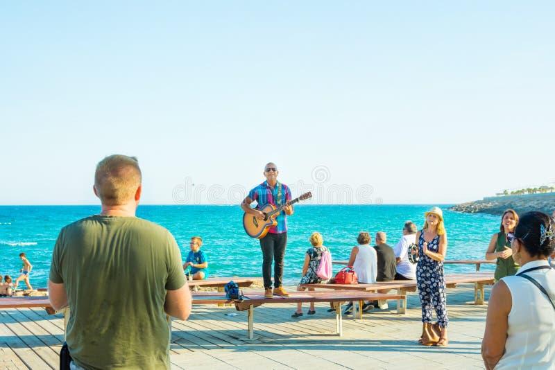 Gatamusikband som utför på sjösidastrandpromenad på solig sommardag Ung man med applådera för åhörare för guitarr sjungande royaltyfri bild
