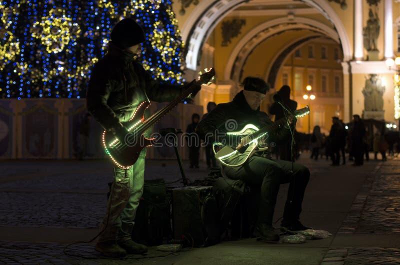 Gatamusiker med den nattbelysning och julgranen fotografering för bildbyråer
