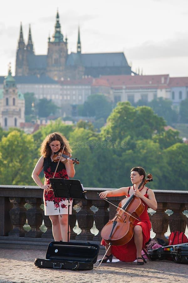Gatamusiker utför med Prague Castel på bakgrund royaltyfri bild