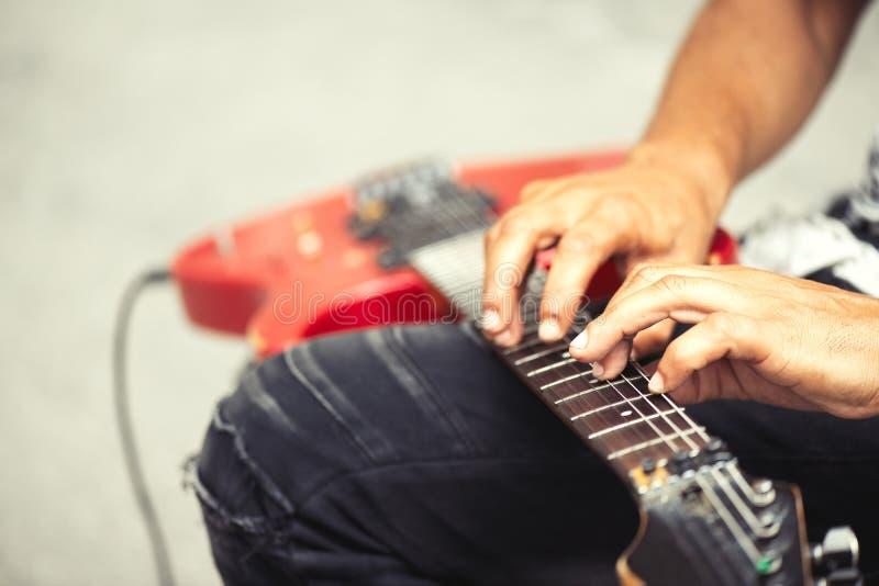 Gatamusikern spelar den elektriska gitarren med hans fingrar i glidbana arkivbild