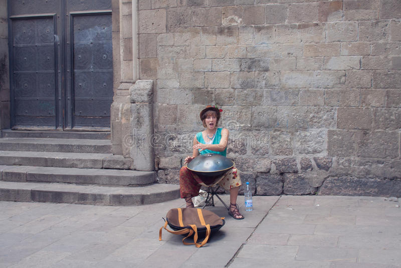 Gatamusikern spelar en musikinstrumenthängning arkivfoto
