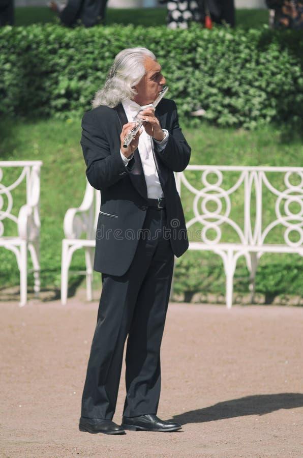 Gatamusikern spelar flöjten på våren royaltyfria foton